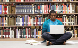 student sitting on floor of library looking at laptop